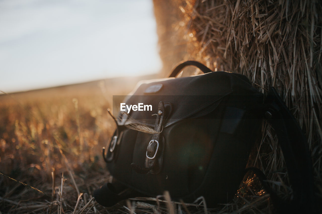 Close-Up Of Bag By Hay Bale On Field