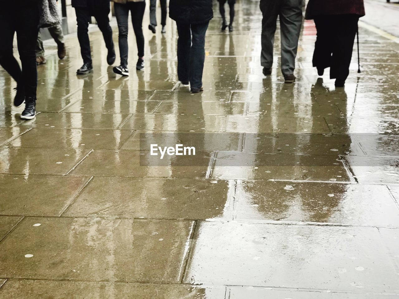 Low section of people walking on wet footpath during rainy season