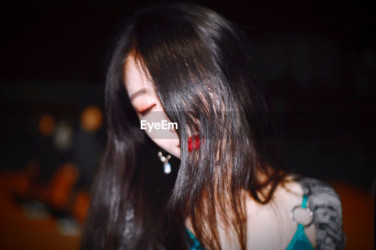 Close-Up Of Young Woman With Long Hair At Night