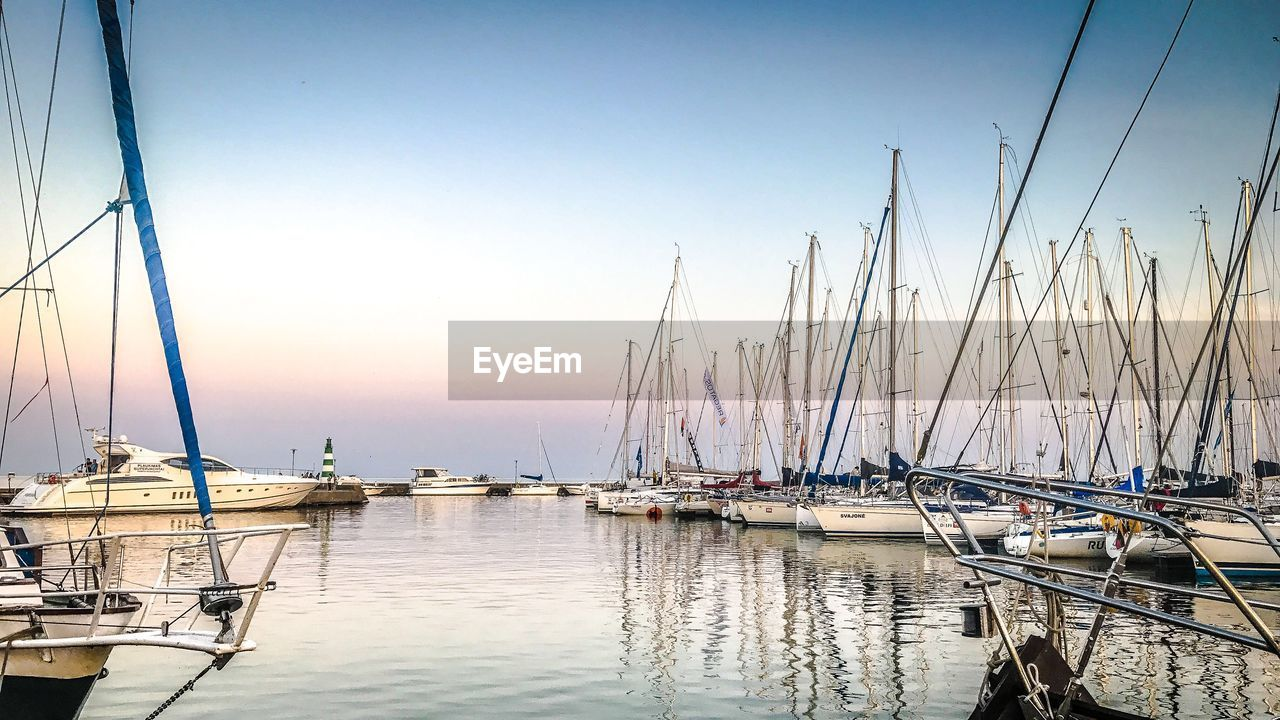 nautical vessel, transportation, water, sky, mode of transportation, sailboat, pole, moored, mast, harbor, sea, no people, clear sky, nature, beauty in nature, reflection, sunset, tranquility, tranquil scene, marina, outdoors, yacht, port