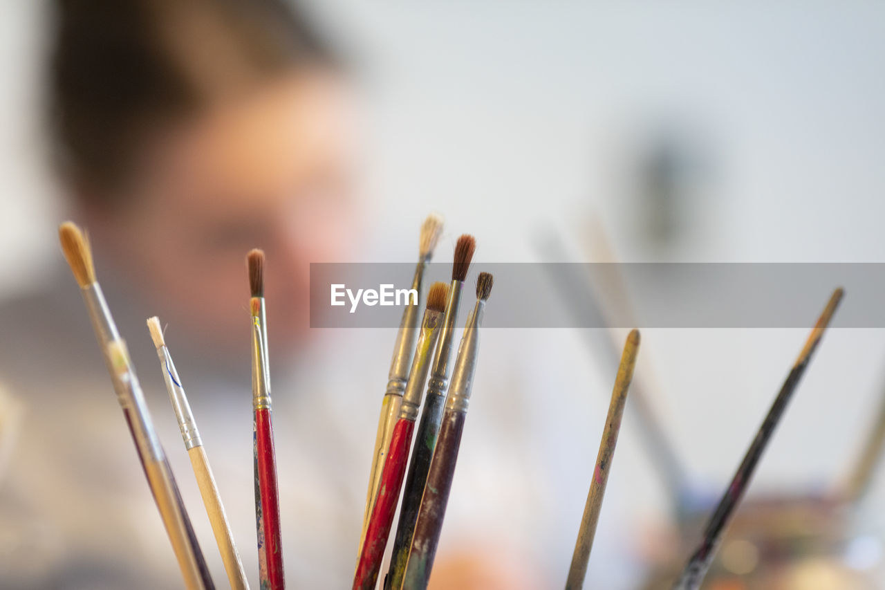 selective focus, focus on foreground, close-up, large group of objects, indoors, incense, still life, creativity, art and craft, one person, brush, day, multi colored, paintbrush, men, craft, skill, leisure activity, spirituality, art and craft equipment