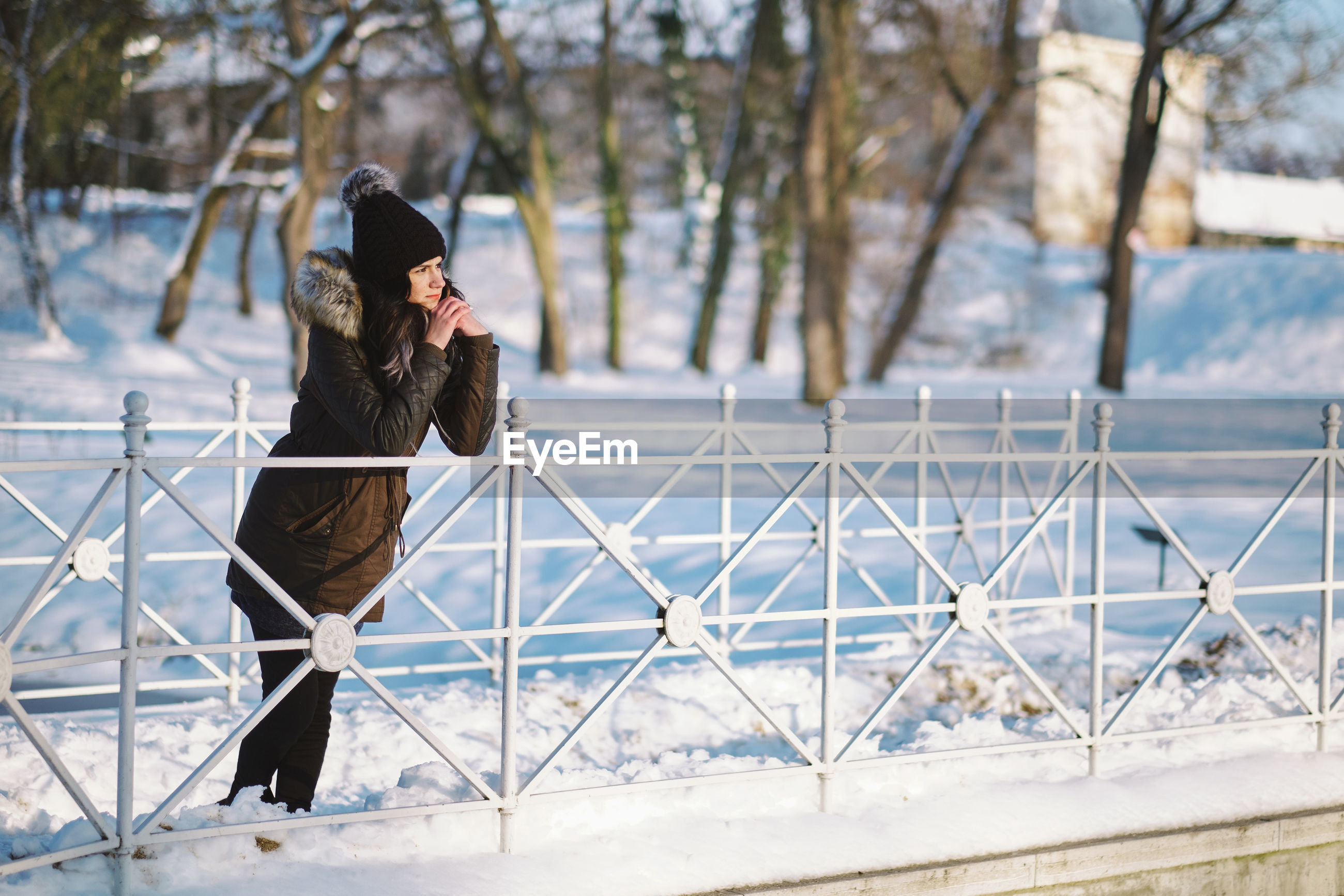 Woman leaning on railing during winter