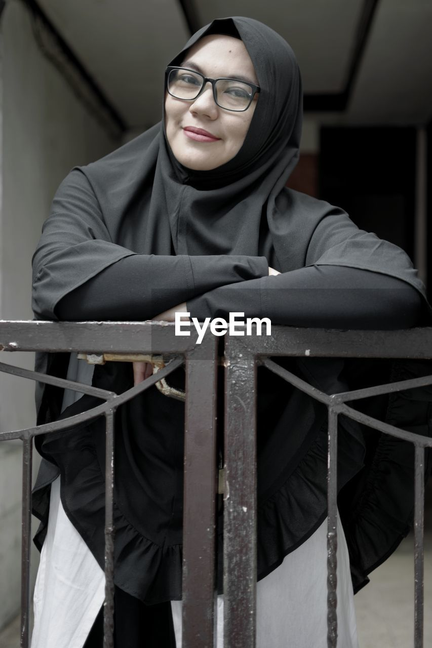 Portrait Of Smiling Woman In Hijab Standing At Railing
