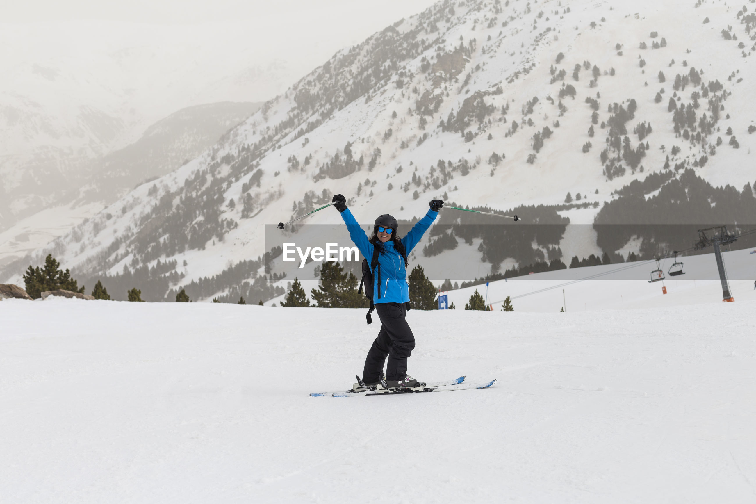 Portrait of smiling woman with arms raised skiing on snowcapped mountain