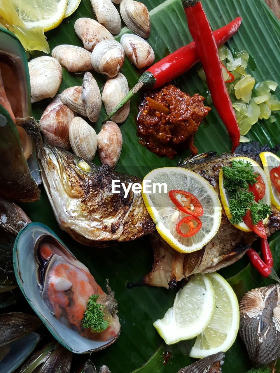 Fried Fish And Animal Shells On Banana Leaf