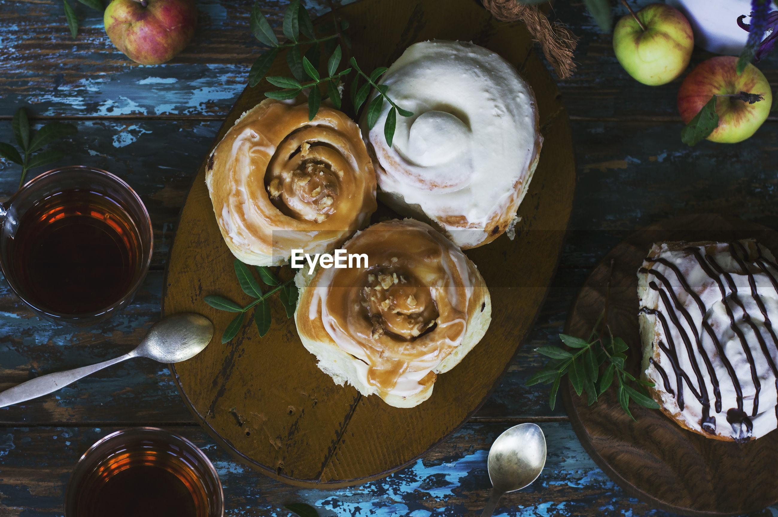 High angle view of cinnamon bun and apples on table