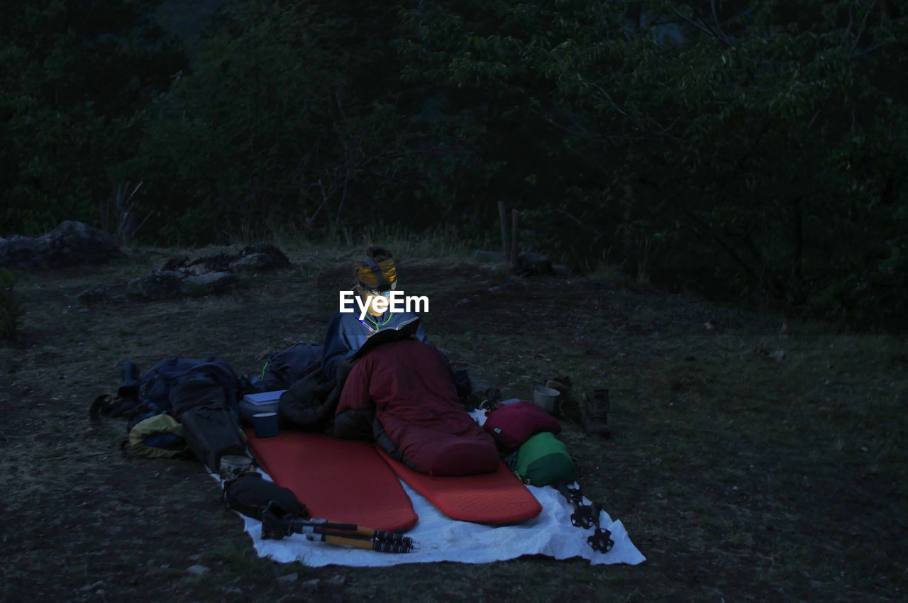 Woman Writing On Book While Camping On Field At Dusk