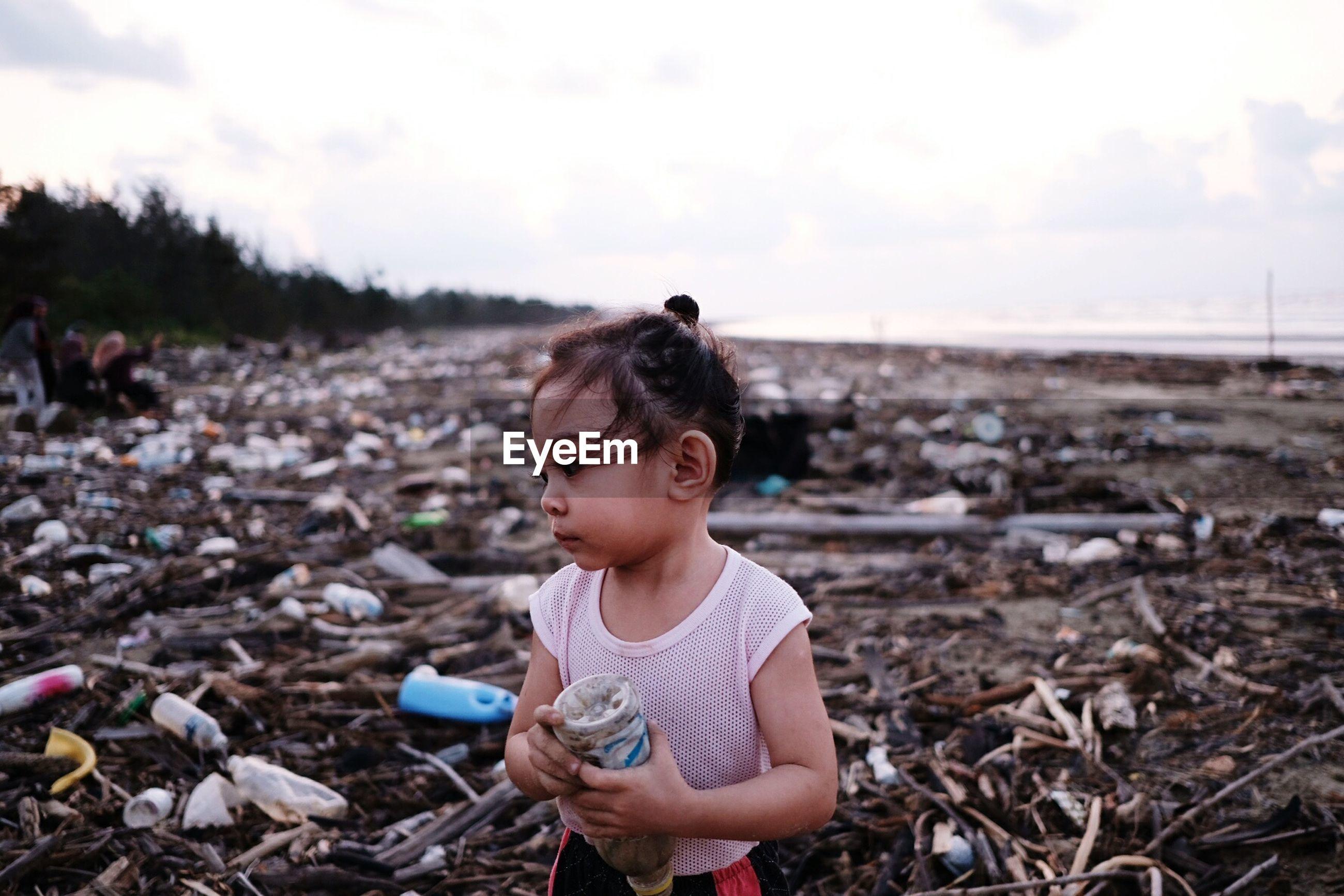 Girl holding bottle at dirty beach