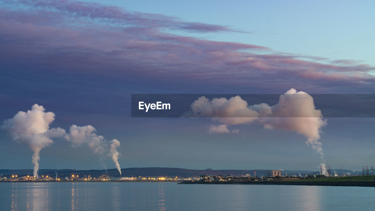 sky, cloud - sky, architecture, water, building exterior, built structure, waterfront, nature, factory, city, smoke - physical structure, smoke stack, pollution, no people, emitting, industry, sea, outdoors, air pollution, cityscape