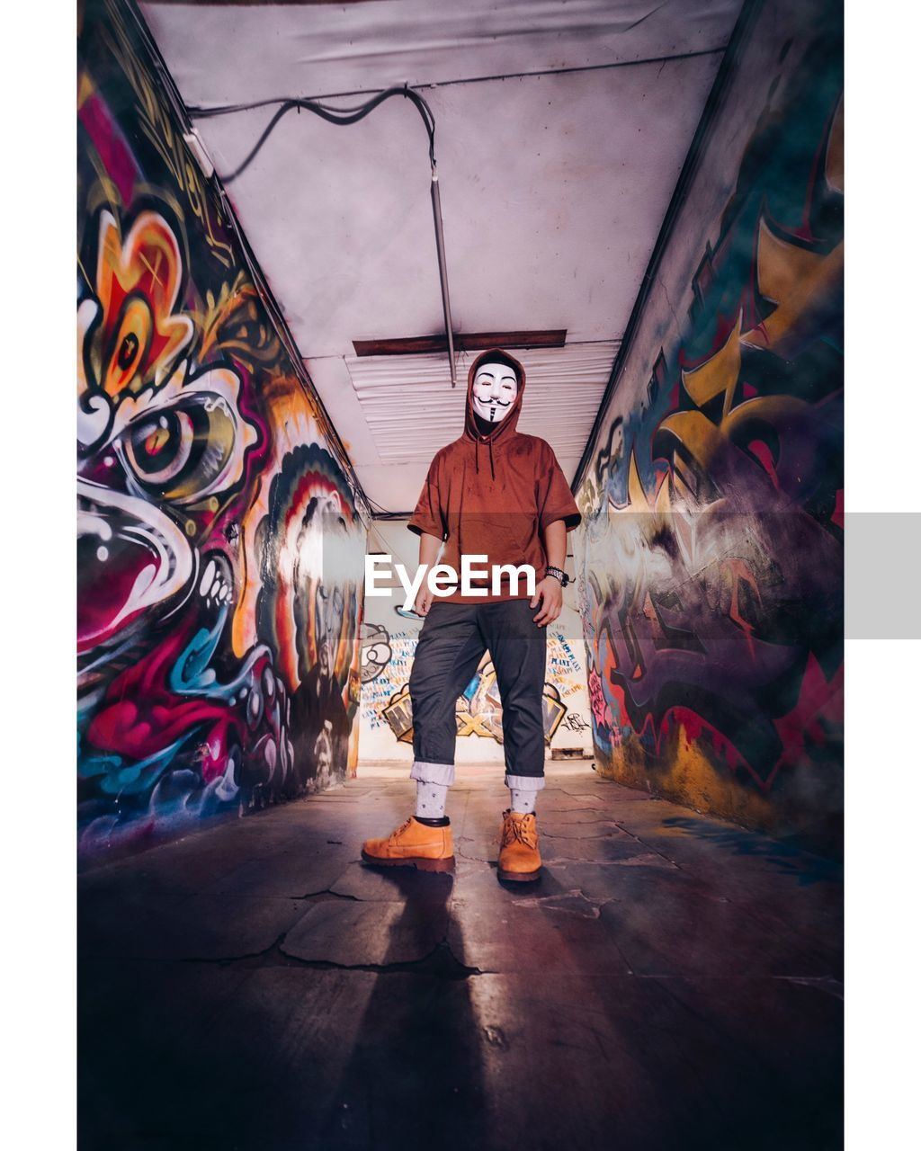 one person, real people, full length, creativity, art and craft, wall - building feature, standing, lifestyles, rear view, graffiti, indoors, casual clothing, men, multi colored, architecture, leisure activity, day, auto post production filter, mural