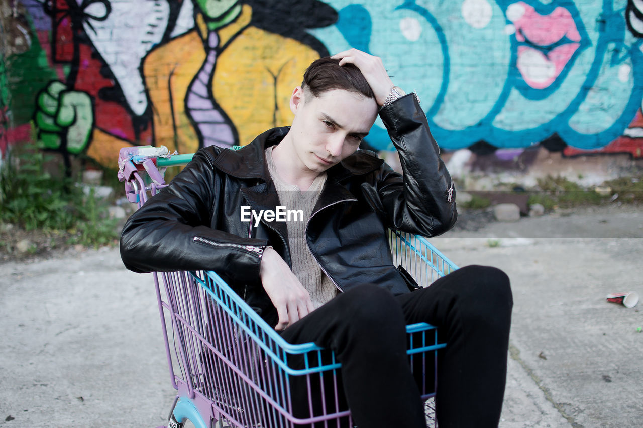 Young Man Sitting In Shopping Cart Against Graffiti On Wall