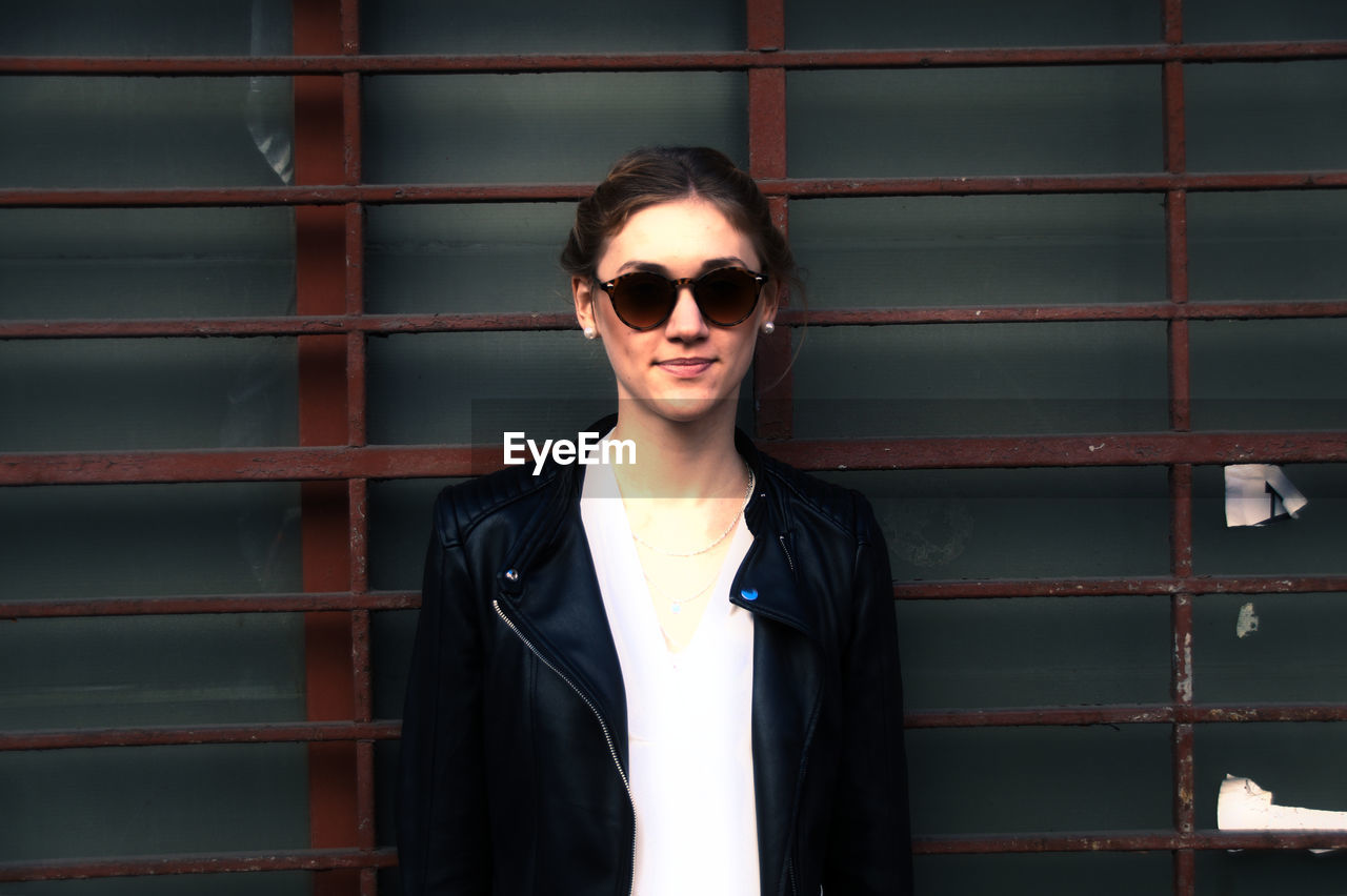 Portrait of young woman wearing sunglasses while standing against wall
