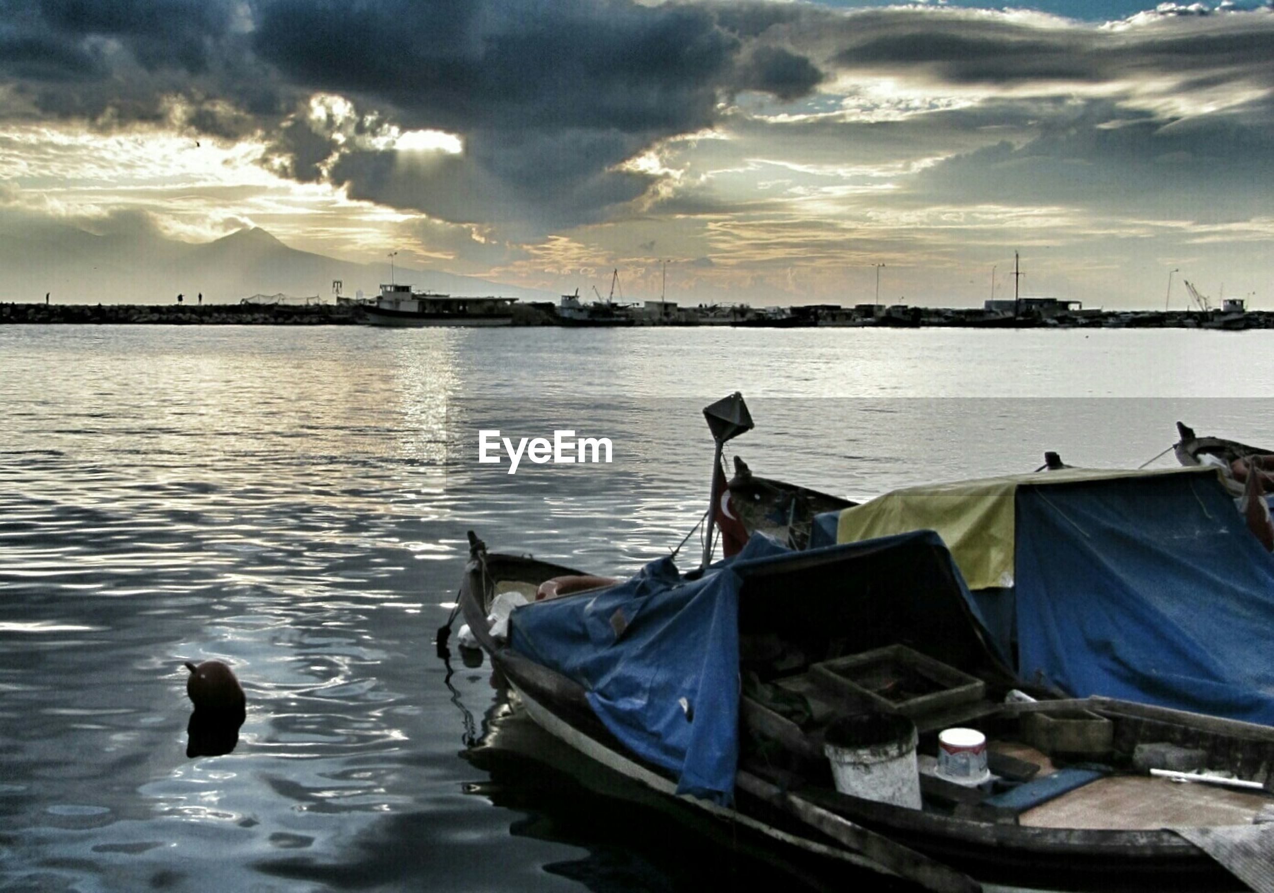 Boats moored in lake against cloudy sky during sunset