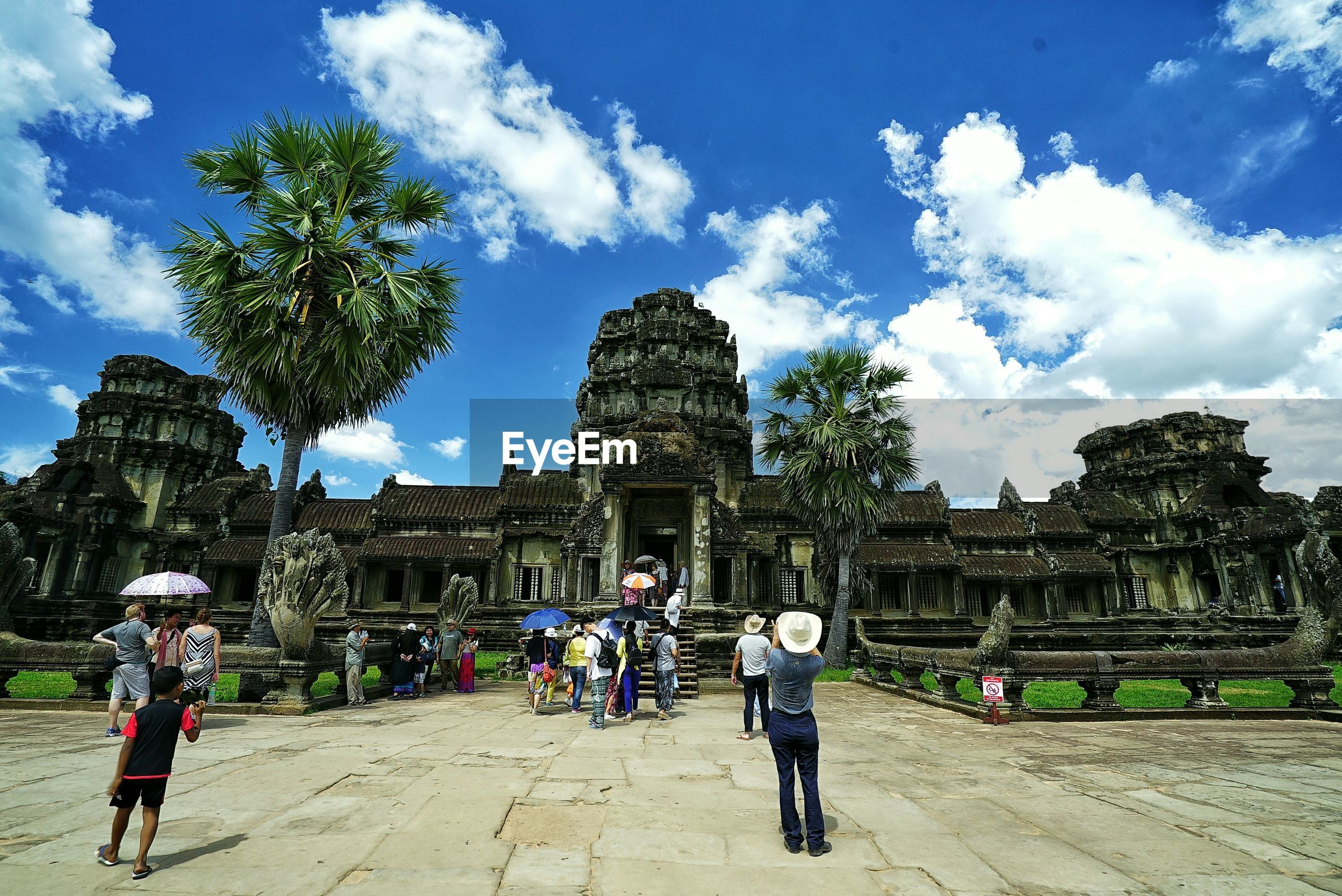 Tourists at angkor wat temple against sky