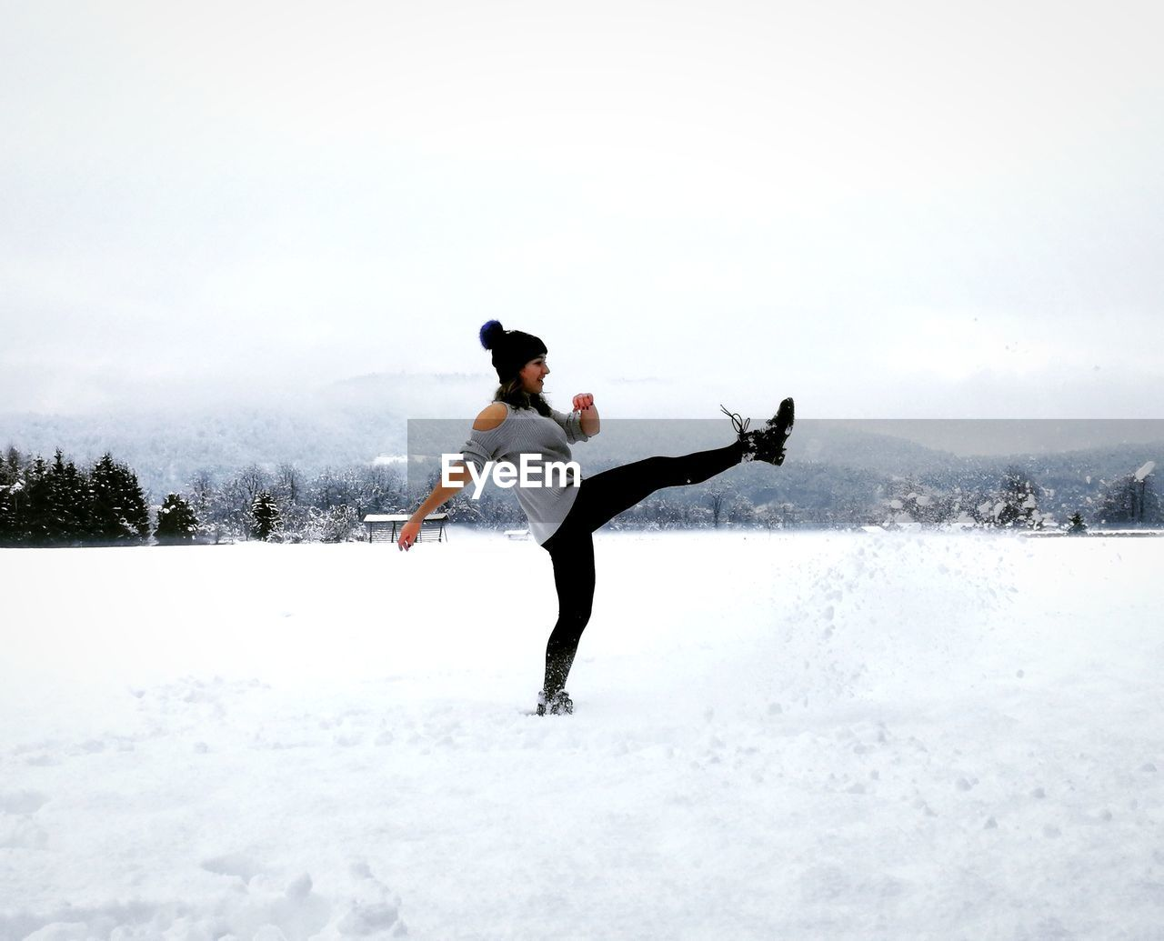 Full Length Of Woman Kicking In Snow Against Sky