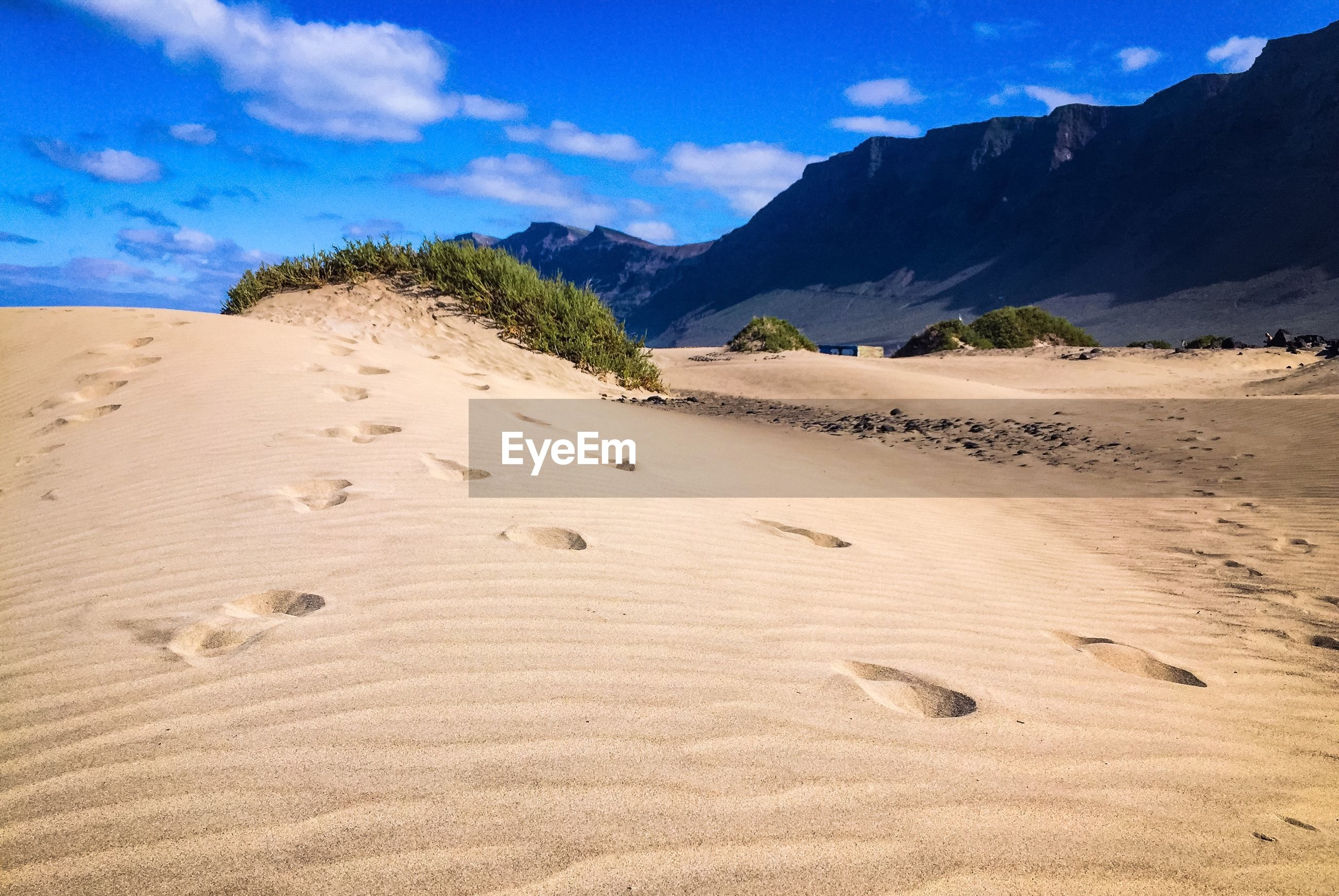 Footprints on sand in desert by mountains against sky