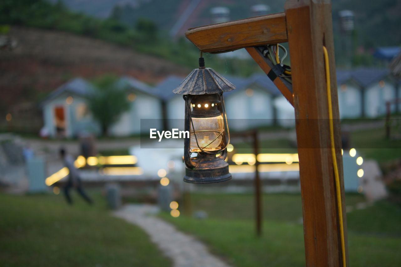 Illuminated Lantern Hanging On Pole Against Landscape