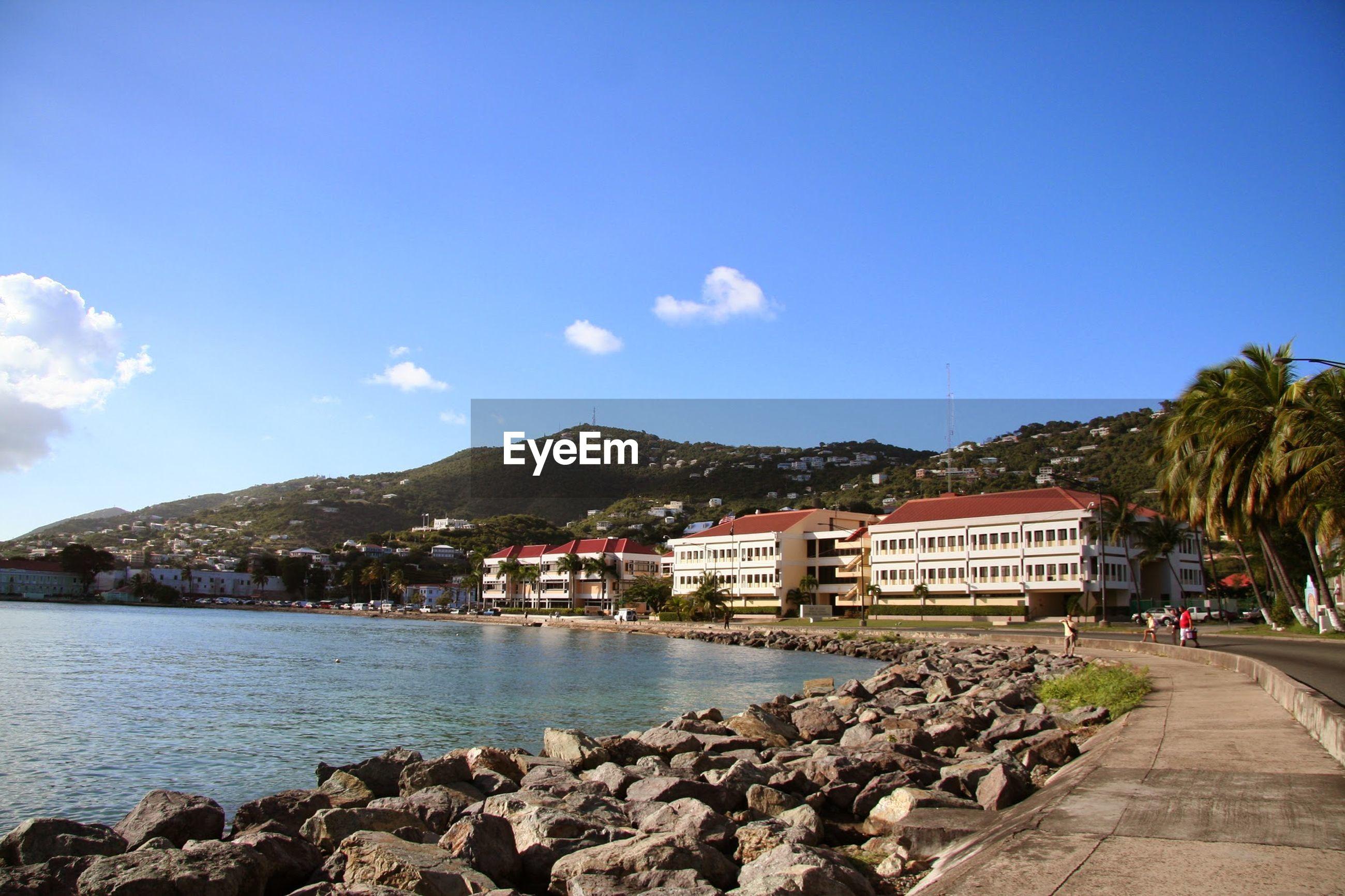 Residential buildings by coastline against blue sky