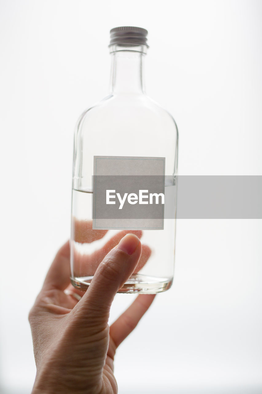 human hand, holding, bottle, human body part, hand, container, one person, finger, human finger, body part, indoors, glass - material, close-up, studio shot, real people, white background, unrecognizable person, transparent, drink, blank