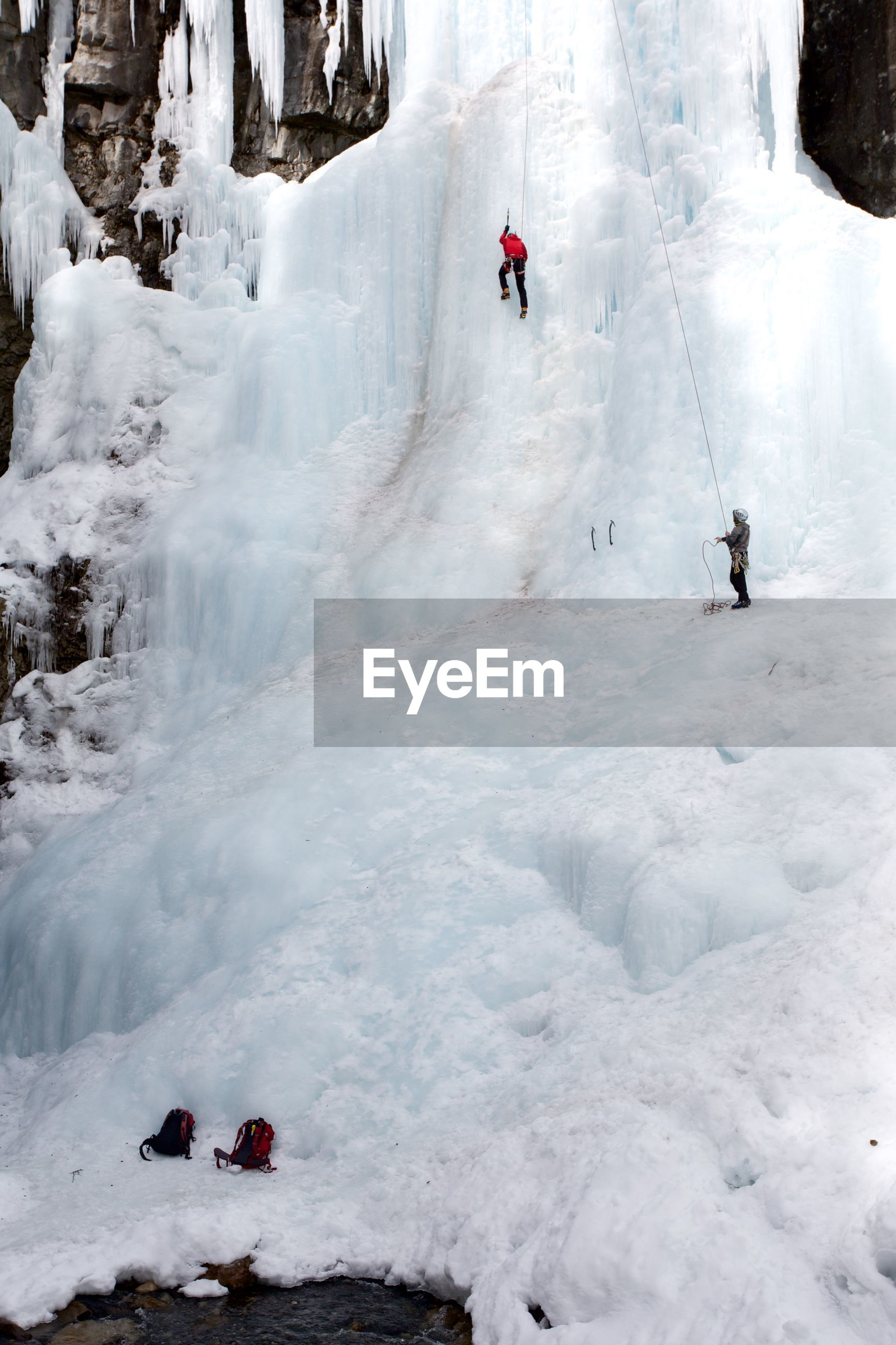 People climbing on snow covered mountain