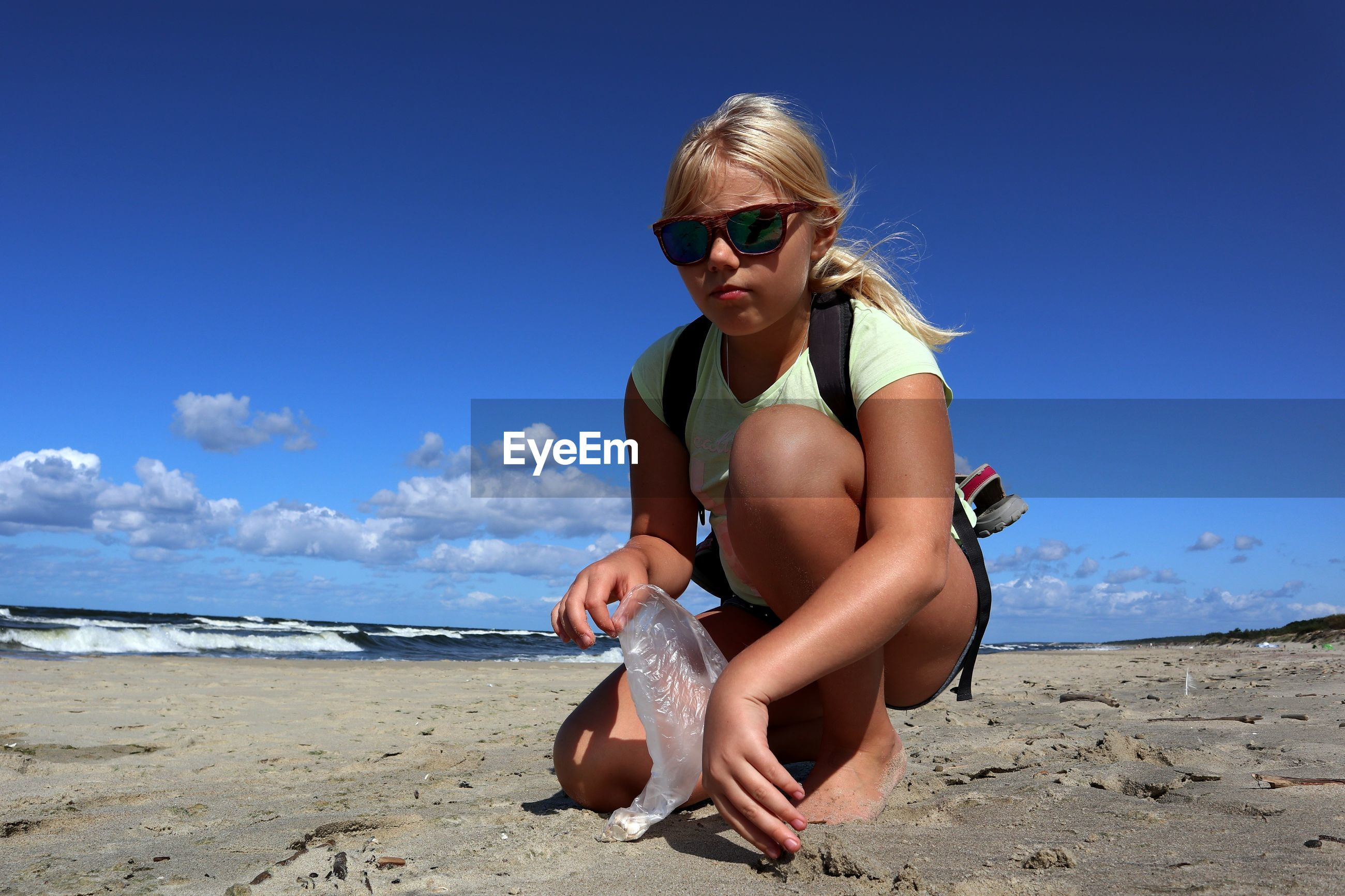 Portrait of girl holding plastic bag while crouching at beach against blue sky