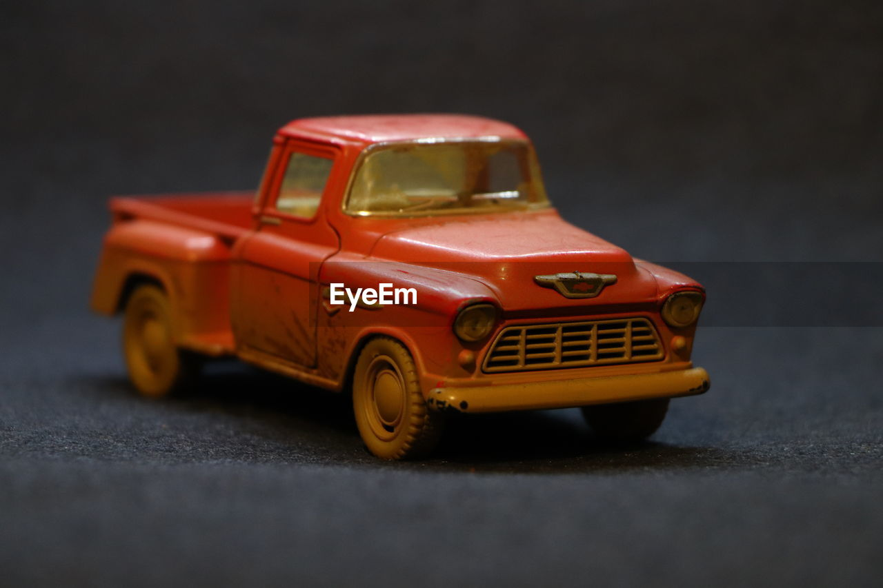 toy car, toy, close-up, car, indoors, no people, still life, red, motor vehicle, mode of transportation, transportation, selective focus, land vehicle, table, plastic, focus on foreground, figurine, single object, road, small, wheel