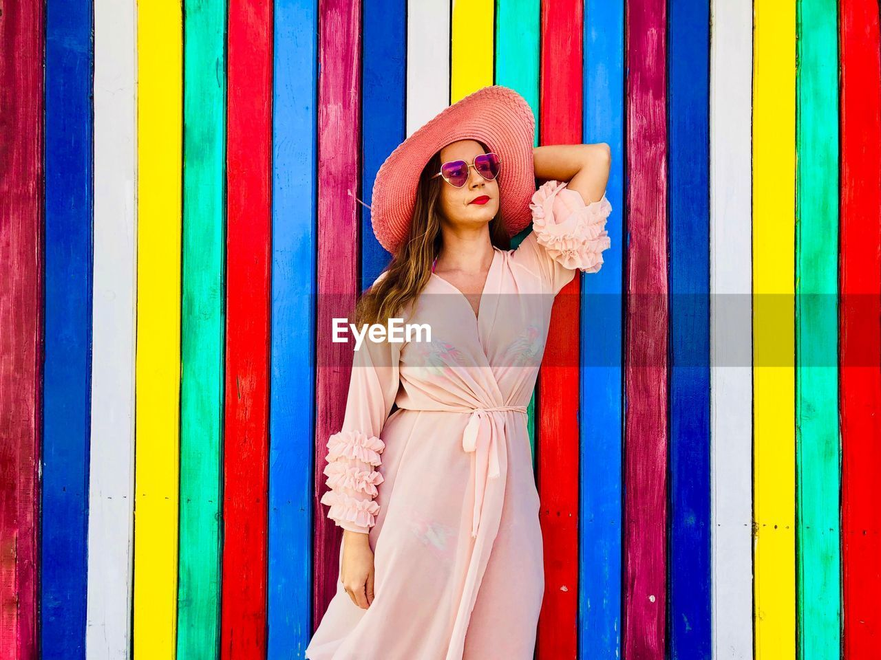 Woman in dress standing against multi colored wall