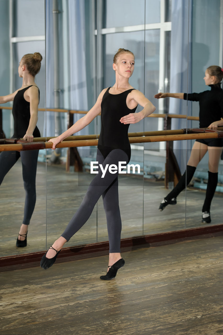 dancing, ballet, ballet dancer, full length, practicing, young adult, indoors, dance studio, exercising, skill, lifestyles, young women, balance, elegance, people, healthy lifestyle, standing, real people, women, limb, human arm