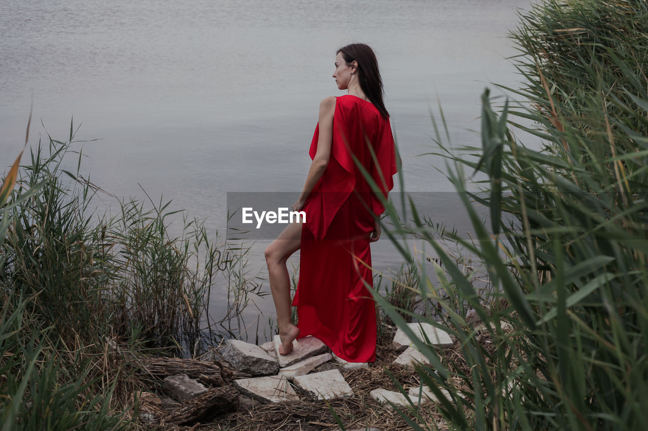 red, one person, young adult, plant, young women, lifestyles, fashion, real people, leisure activity, water, nature, beauty, land, standing, grass, beautiful woman, dress, casual clothing, outdoors, contemplation, hairstyle