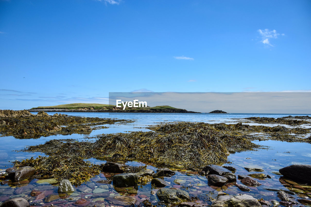 nature, water, tranquility, tranquil scene, beauty in nature, rock - object, sea, no people, scenics, outdoors, day, beach, blue, sky, horizon over water