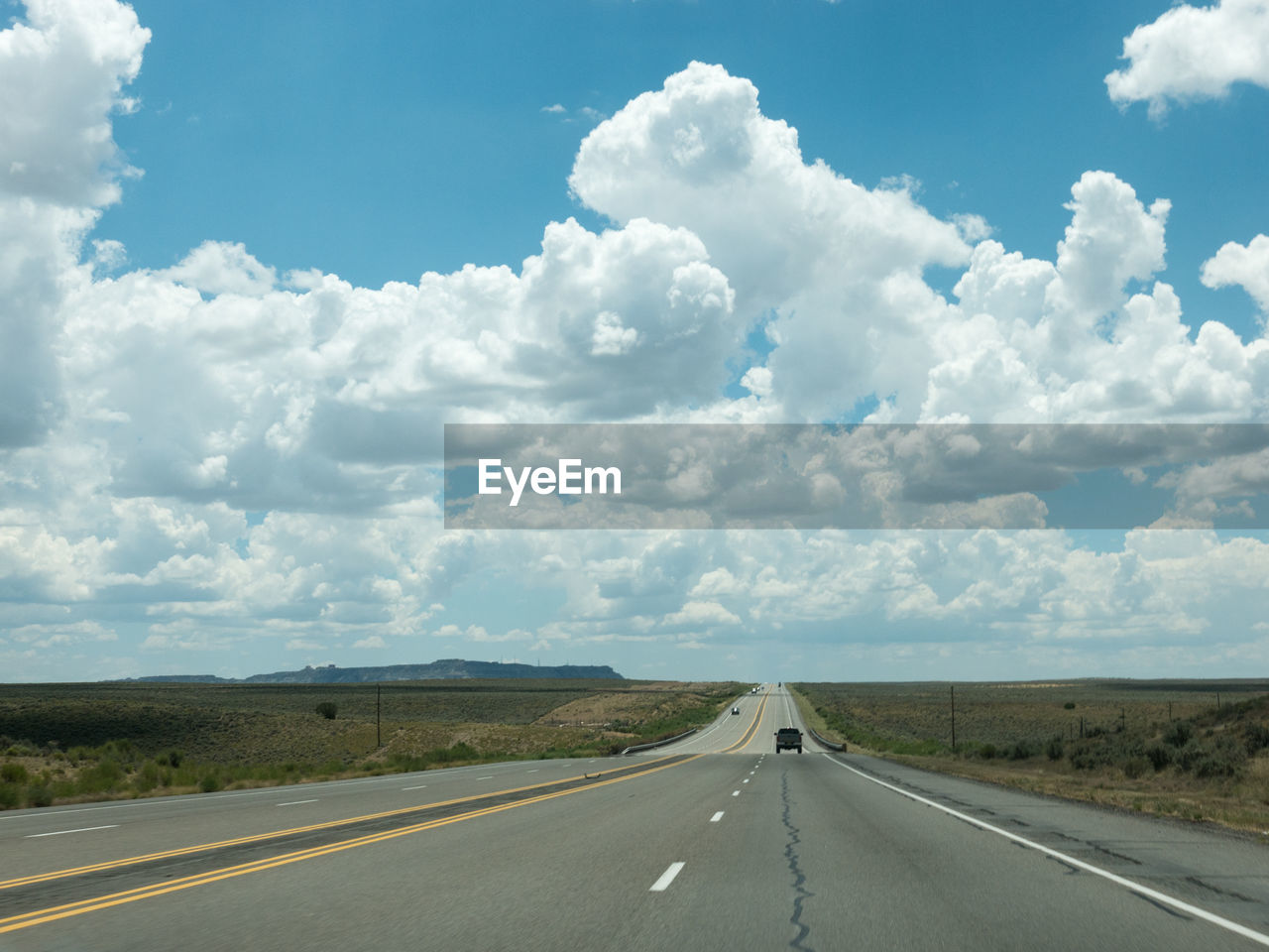 road, cloud - sky, sky, transportation, direction, the way forward, road marking, marking, symbol, day, sign, nature, environment, vanishing point, landscape, no people, diminishing perspective, country, land, non-urban scene, outdoors, dividing line, long