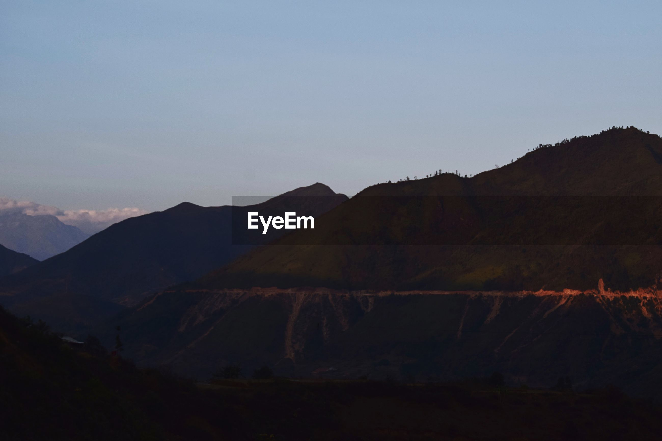 SCENIC VIEW OF SILHOUETTE MOUNTAIN AGAINST SKY AT DUSK