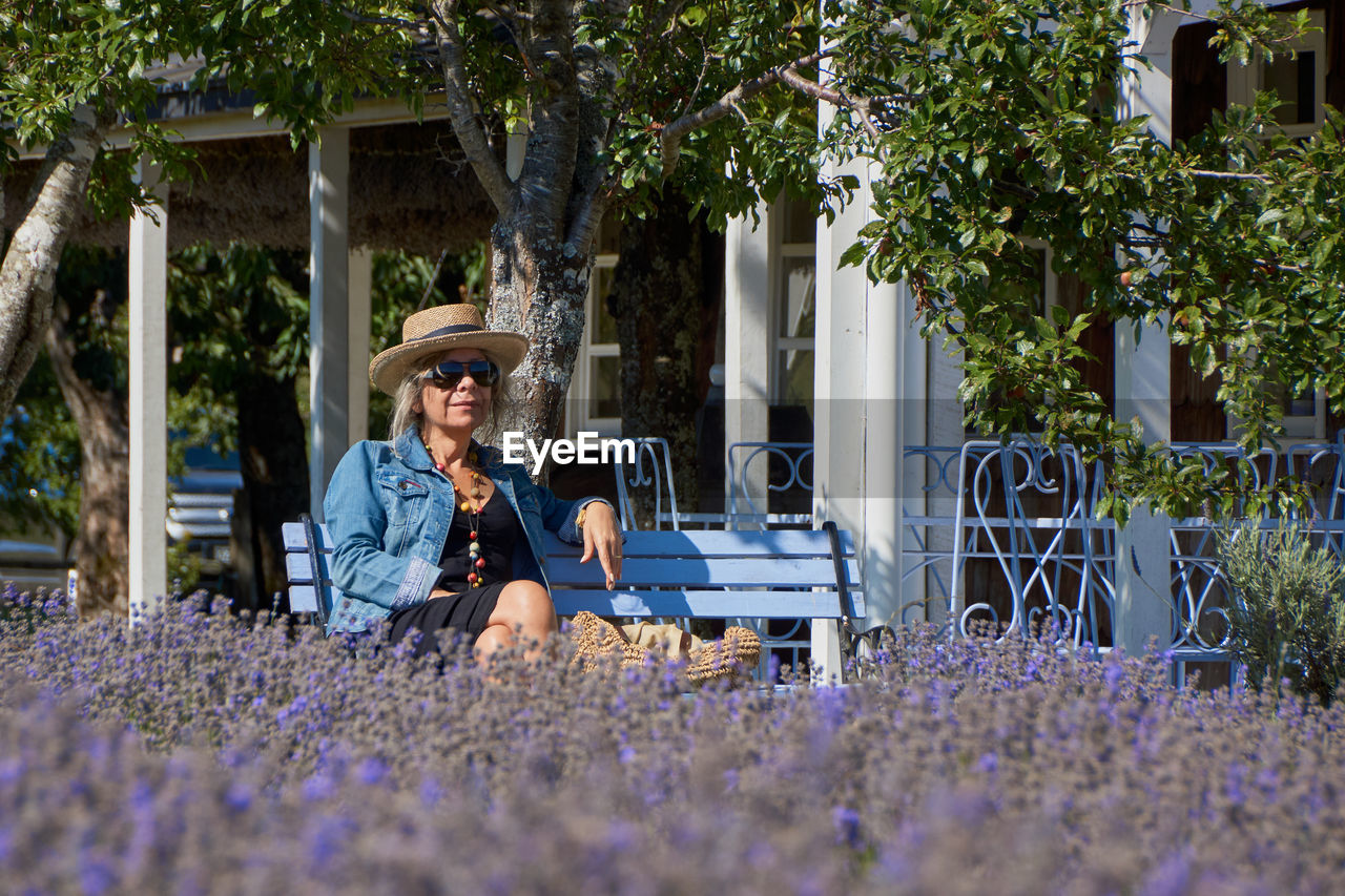 Mature Woman Wearing Sunglasses And Hat While Sitting On Bench In Park
