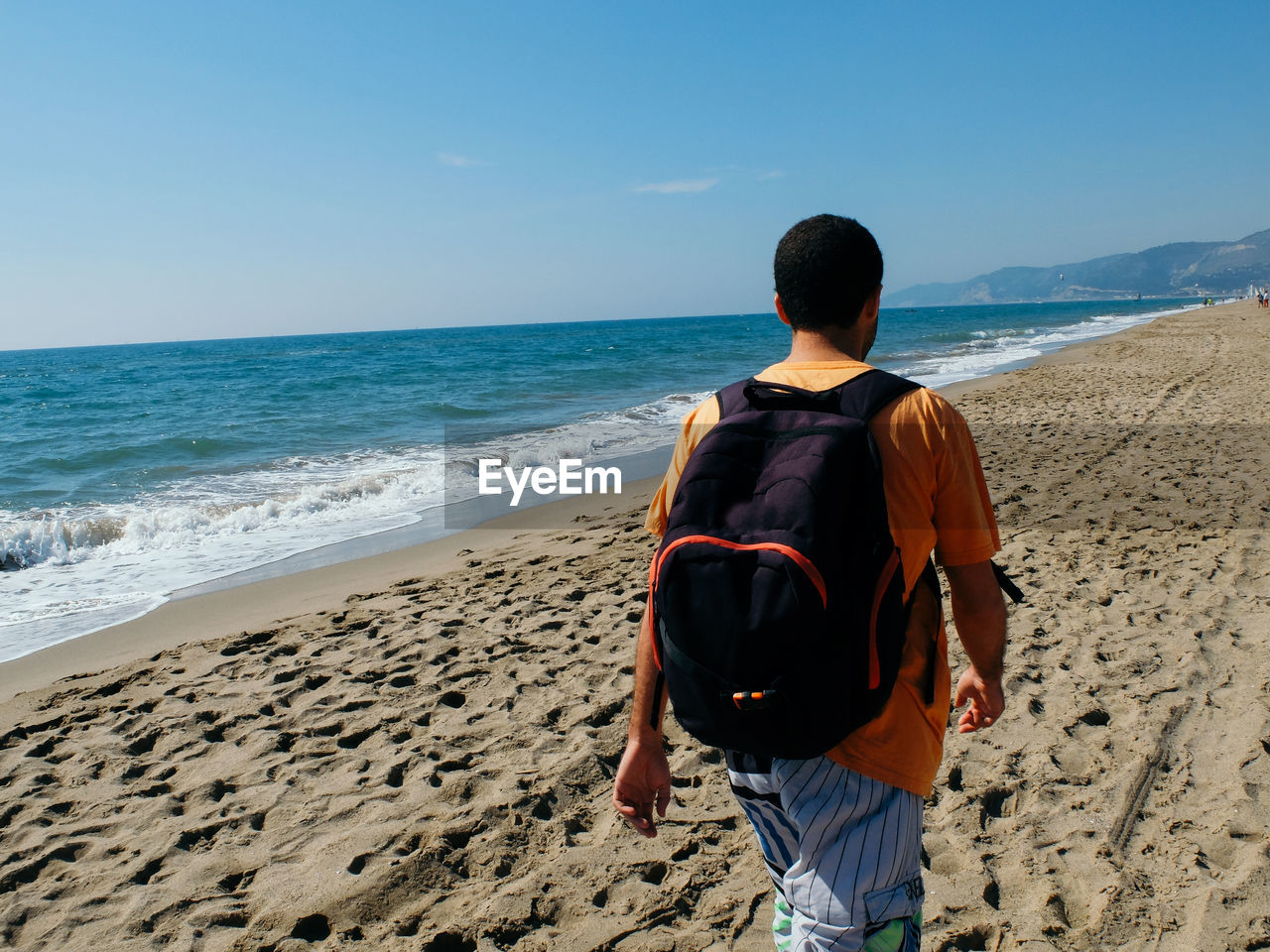 Rear view of man with backpack walking at beach against blue sky during sunny day