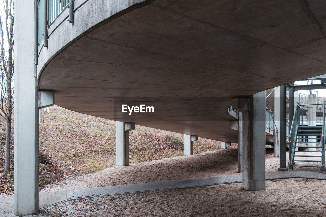 built structure, architecture, architectural column, bridge, bridge - man made structure, no people, connection, day, underneath, below, transportation, outdoors, in a row, building exterior, building, city, road, concrete, overpass, ceiling