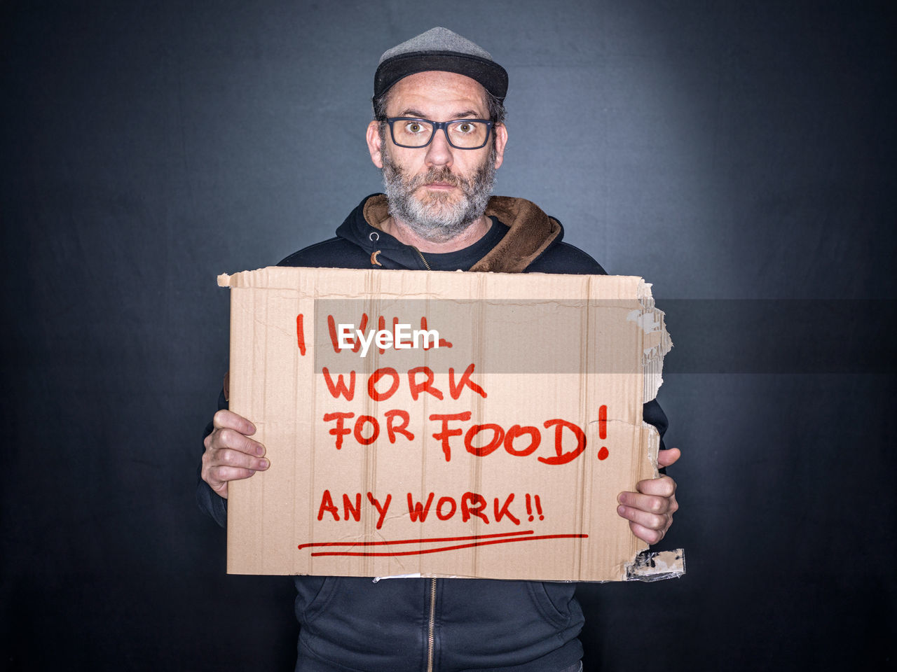 cardboard, eyeglasses, glasses, one person, holding, sign, communication, studio shot, indoors, social issues, adult, black background, text, sadness, gray, men, mature adult, depression - sadness, unemployment, hopelessness