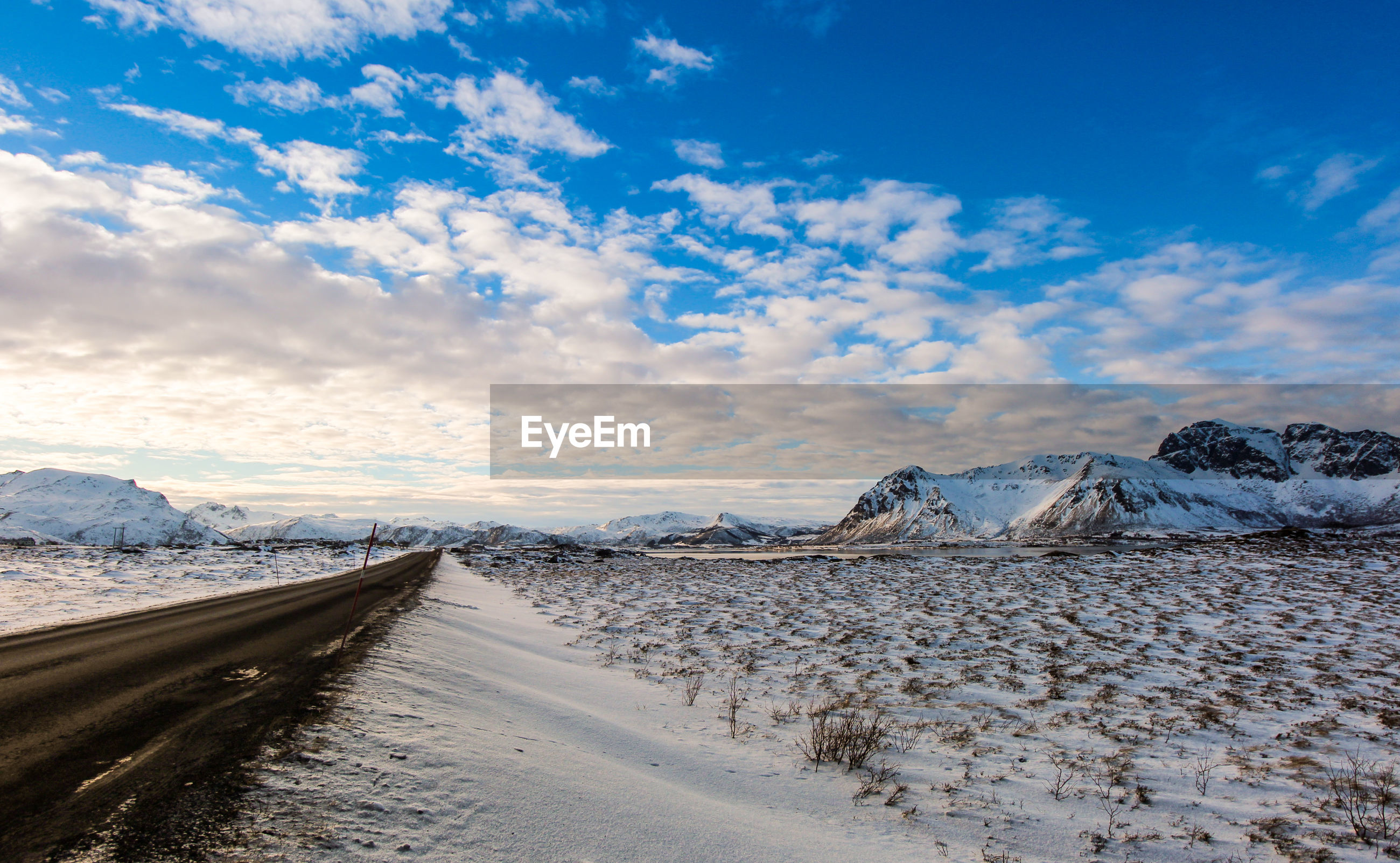 SNOW COVERED ROAD BY SNOWCAPPED MOUNTAINS AGAINST SKY
