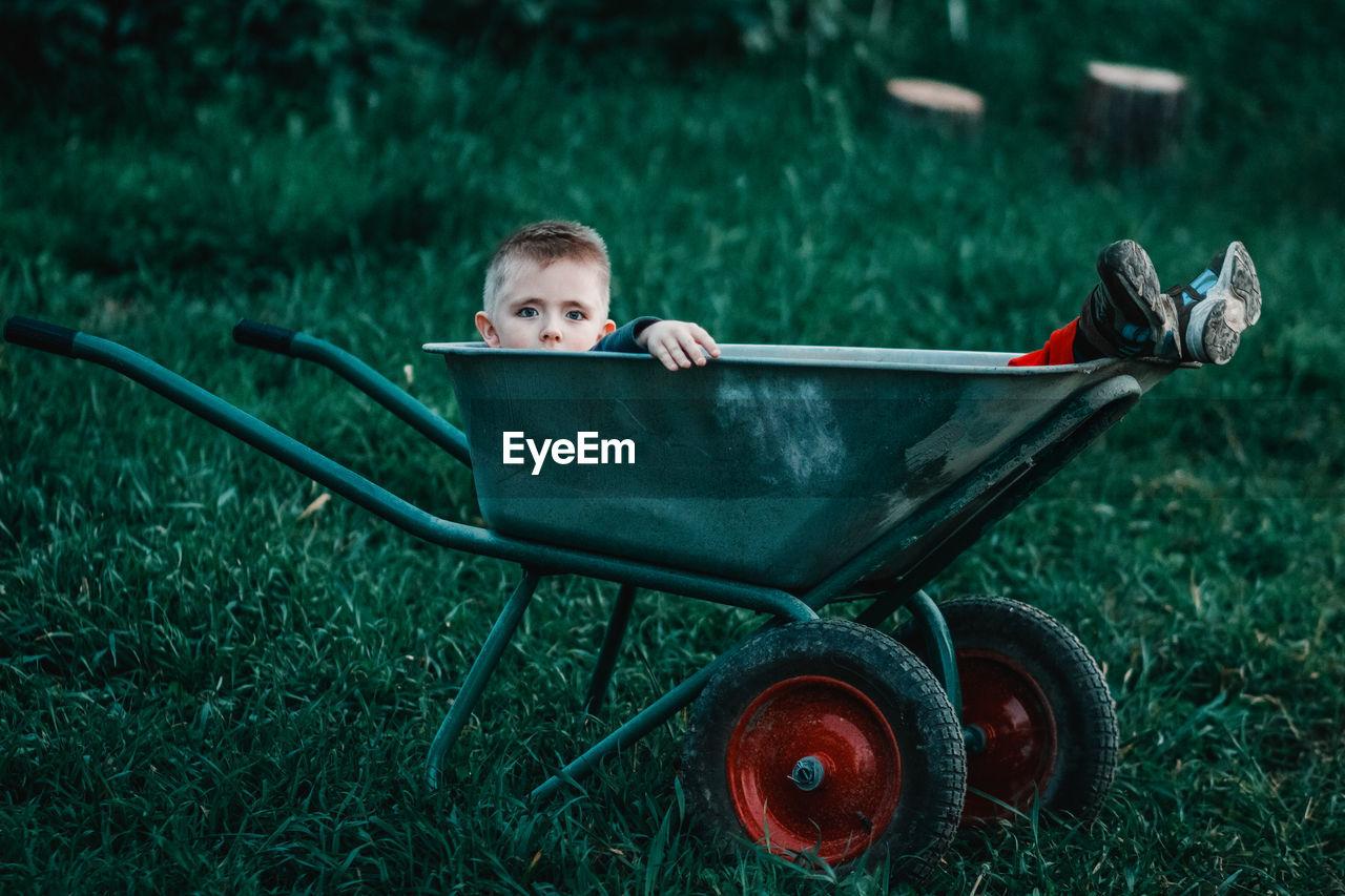 Portrait Of Boy Sitting In Wheelbarrow On Field