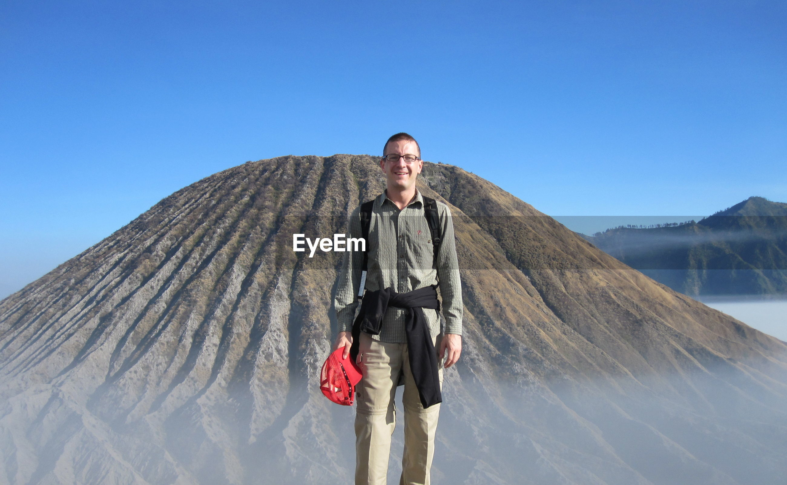 Portrait of man standing against mountain and clear blue sky