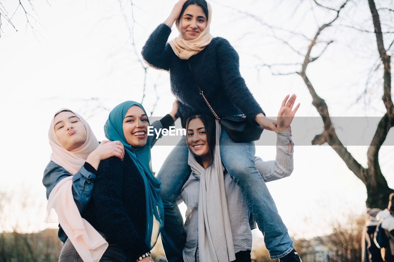young women, real people, young adult, lifestyles, winter, portrait, warm clothing, leisure activity, smiling, people, looking at camera, togetherness, front view, standing, clothing, cold temperature, happiness, emotion, tree, day, outdoors, scarf, teenager