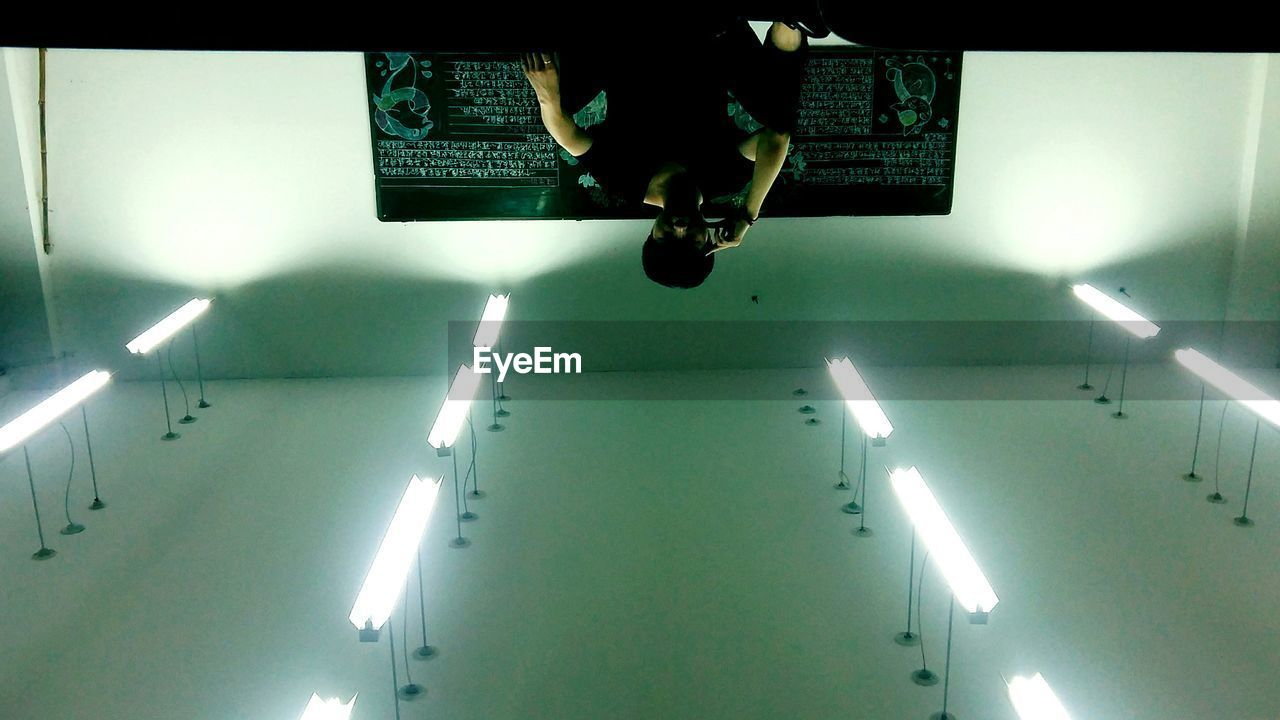 ceiling, indoors, illuminated, real people, low angle view, one person, low section, men, technology, day, people