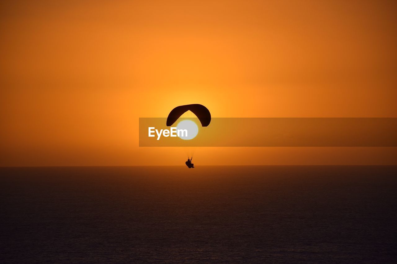 sunset, sky, scenics - nature, orange color, horizon over water, beauty in nature, sea, horizon, silhouette, waterfront, water, unrecognizable person, sun, tranquil scene, tranquility, nature, sport, idyllic, adventure, outdoors