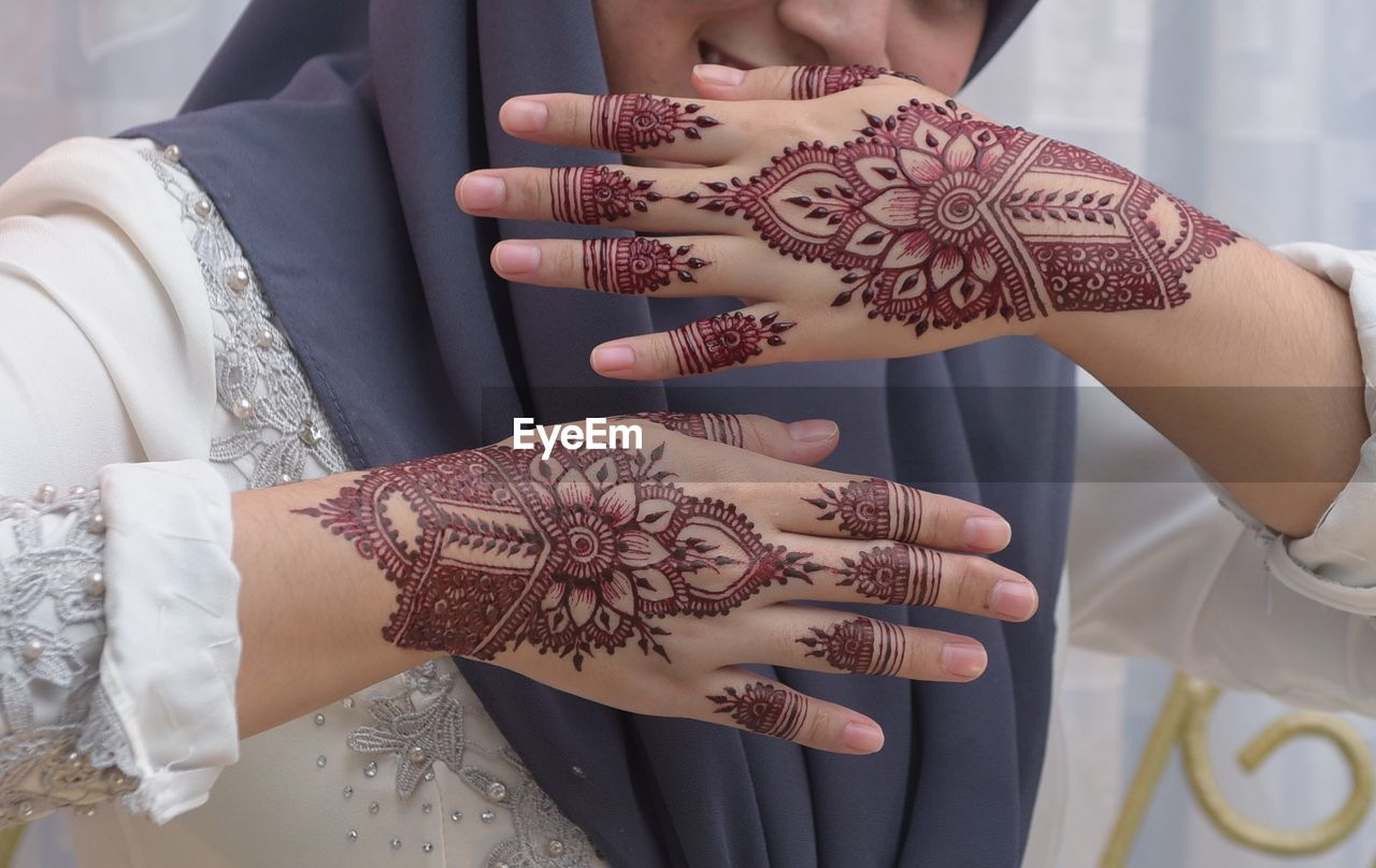 midsection, real people, life events, celebration, human hand, bride, wedding, tattoo, cultures, wedding dress, focus on foreground, wedding ceremony, celebration event, close-up, women, indoors, lifestyles, bridegroom, togetherness, ceremony, two people, groom, day