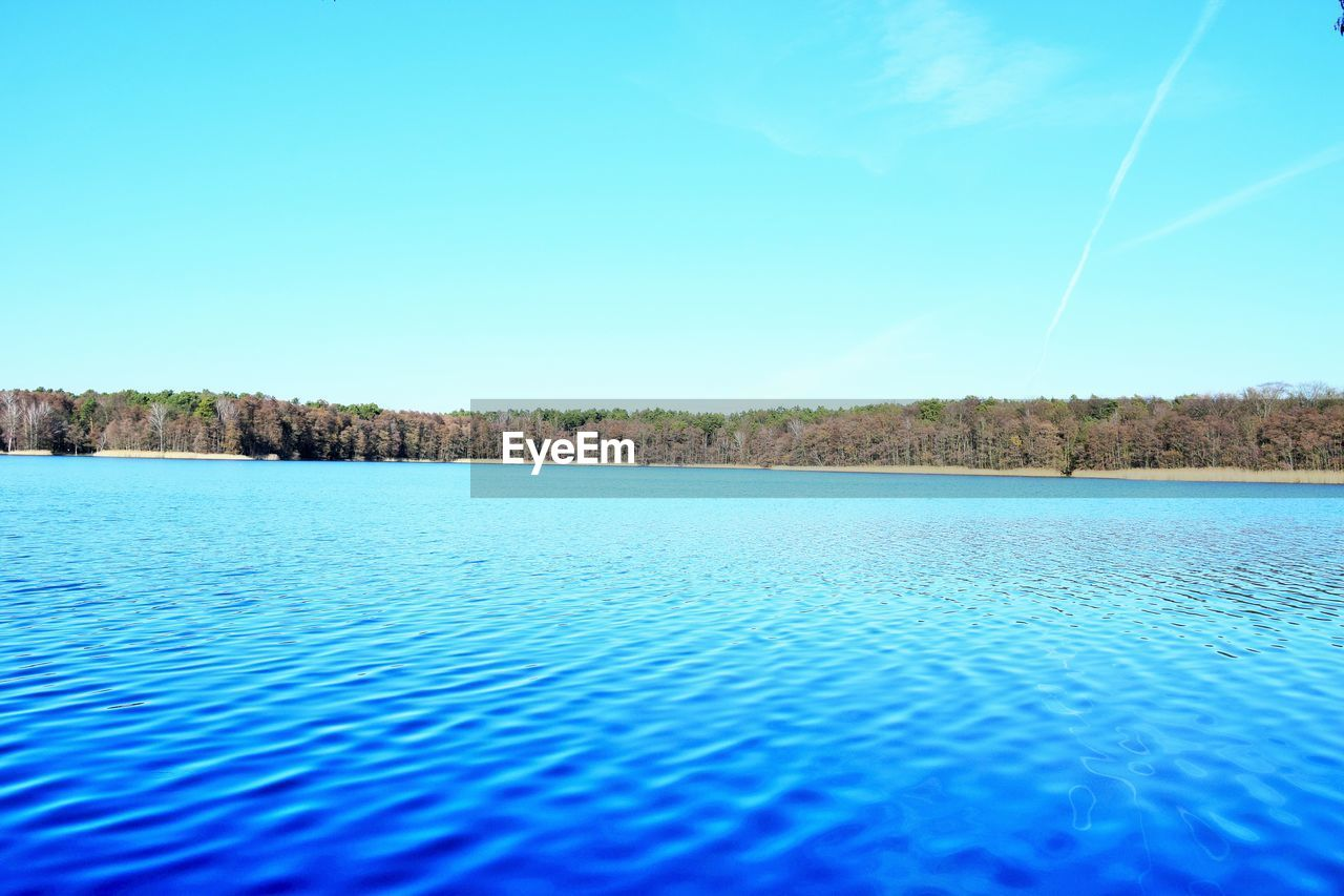 blue, sky, tranquility, tranquil scene, water, beauty in nature, scenics - nature, waterfront, nature, copy space, no people, tree, day, vapor trail, clear sky, idyllic, plant, non-urban scene, lake, surface level, turquoise colored