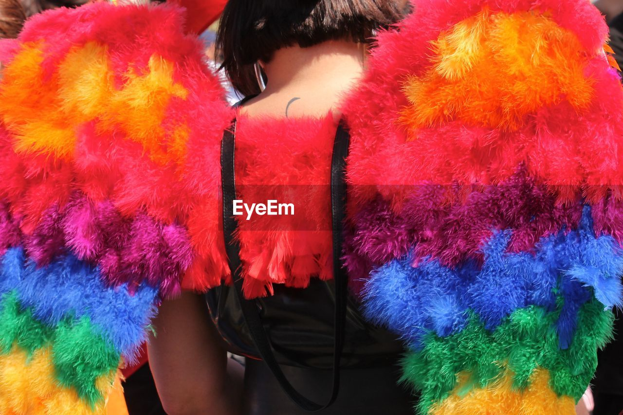 Rear view of woman wearing colorful angel wings during gay pride parade