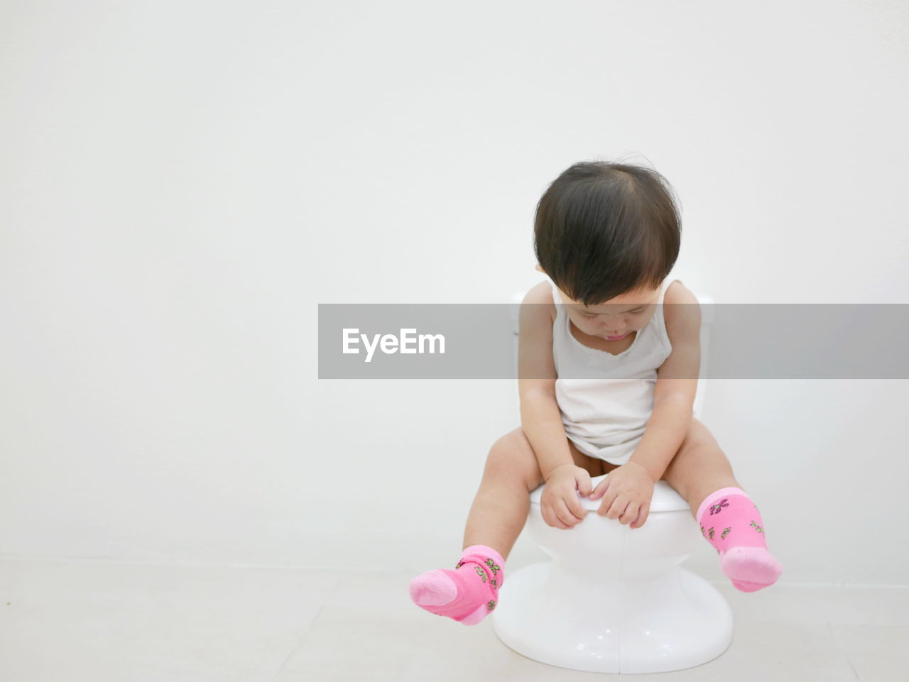 Cute girl sitting on toilet bowl against white background