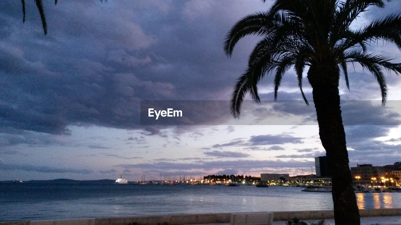 palm tree, sky, cloud - sky, dusk, tree, water, sea, nature, scenics, beach, outdoors, beauty in nature, no people, sunset, silhouette, building exterior, architecture, day