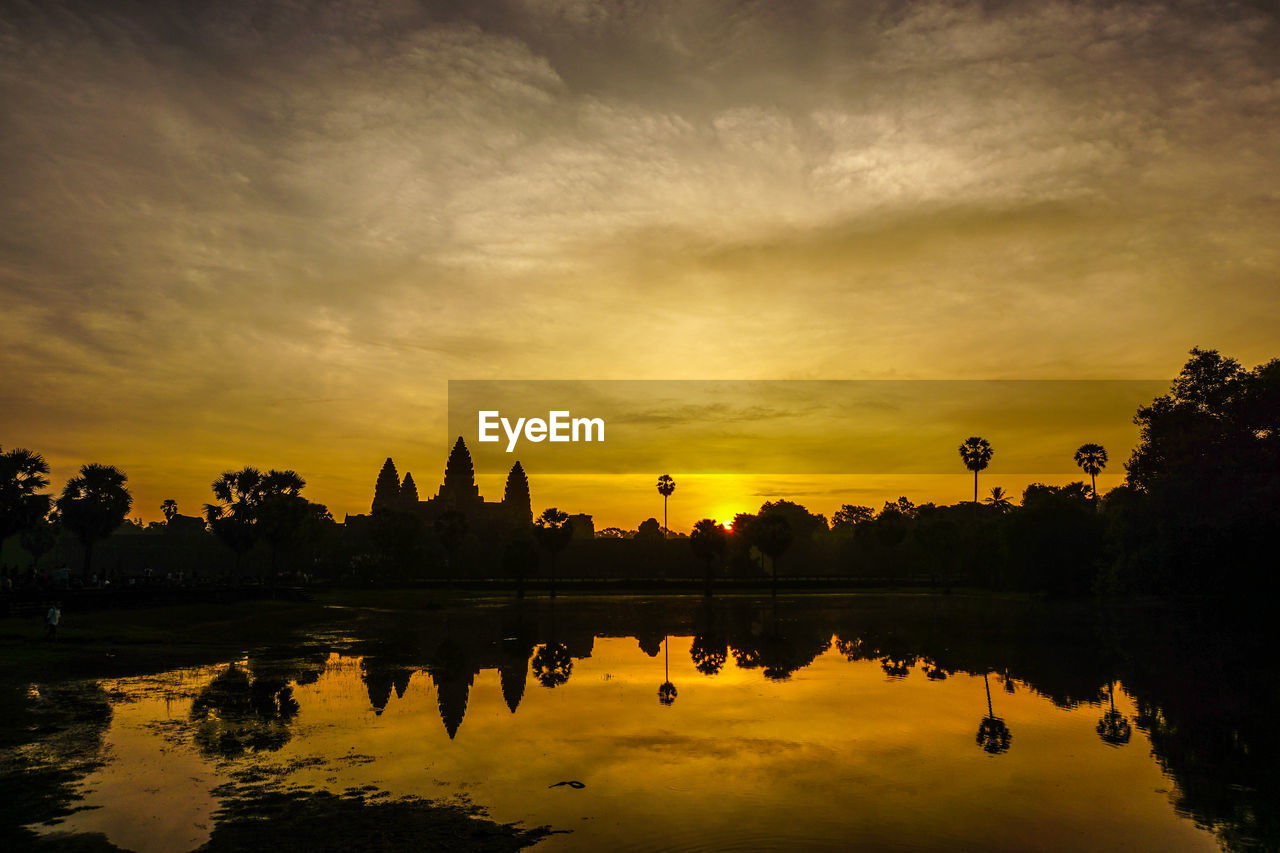 sunset, reflection, sky, architecture, built structure, cloud - sky, silhouette, building exterior, orange color, travel destinations, tree, water, history, religion, spirituality, travel, sun, lake, outdoors, beauty in nature, nature, no people, scenics, ancient civilization, day