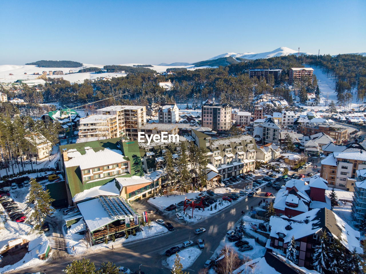 building exterior, architecture, built structure, city, sky, high angle view, residential district, building, mountain, nature, cityscape, crowd, day, snow, crowded, sunlight, winter, blue, cold temperature, community, outdoors, townscape