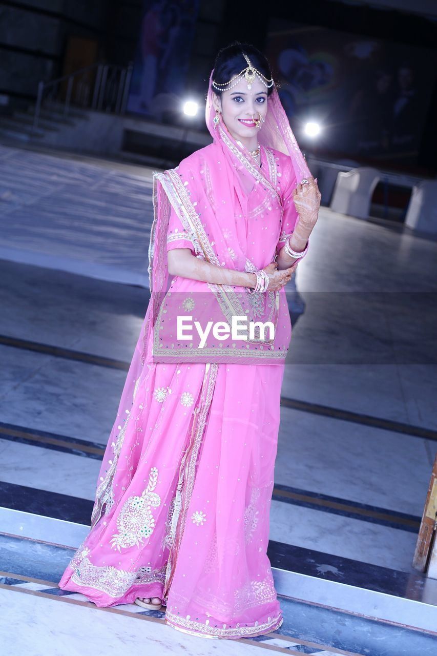 Portrait Of Young Woman Wearing Pink Sari And Jewelry Standing At Pavement
